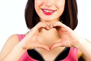 Female hands in the form of heart on the background of a smile