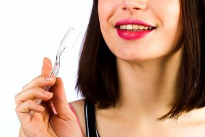 Toothbrush in a female hand on the background of the person