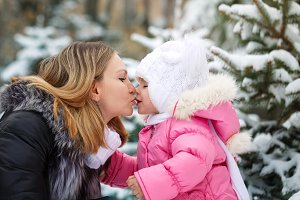 Mother and daughter. Winter kiss.