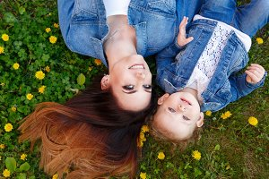 Mother and daughter lying on lawn