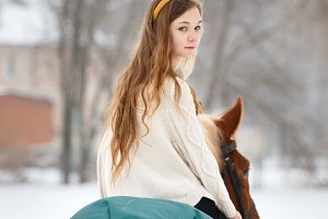 Young girl enjoying horseback riding in winter
