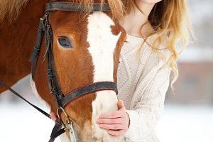 Young teenage girl with horse in winter park