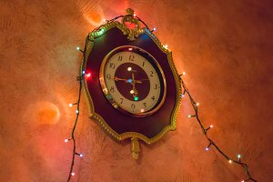 Christmas lights on the old clock. Red wall.