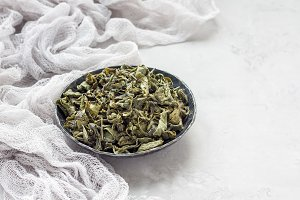 Dry green tea leaves on metal plate, horizontal, copy space