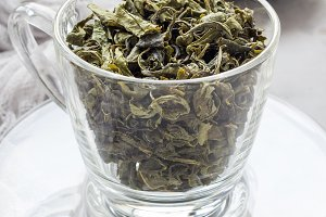 Dry green tea leaves in glass cup and on background, vertical