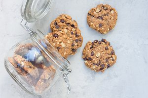 Flourless gluten free peanut butter, oatmeal and chocolate chips cookies in glass jar, top view, horizontal