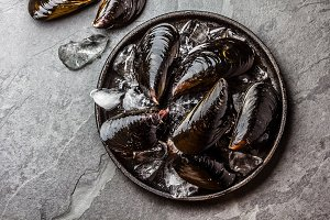 Fresh uncooked big mussels on ice. Slate background. Top view