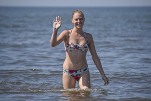 Blond girl in a bikini coming out of the sea water. Beautiful young woman in a colorful bikini on sea background