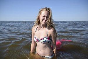 Blond girl in a bikini standing in the sea water. Beautiful young woman in a colorful bikini on sea background.