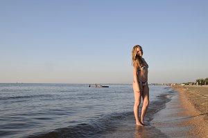 Blond girl in a bikini on the beach. Beautiful young woman in a colorful bikini on sea background