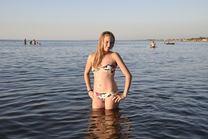 Blond girl in a bikini standing in the sea water. Beautiful young woman in a colorful bikini on sea background