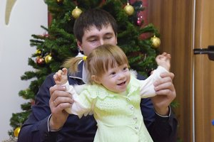 Year-old girl with dad in the background of the Christmas tree. A child with gray eyes and blond hair