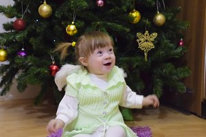 One year old baby girl sitting on the floor near a Christmas tree .. A child plays. Blonde little girl