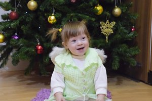 One year old baby girl sitting on the background of the Christmas tree. A child with gray eyes and blond hair
