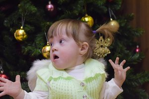 Surprised girl. Child Mimicry. Girl throws up his hands. One year old baby girl sitting on the background of the Christmas tree. A child with gray eyes and blond hair