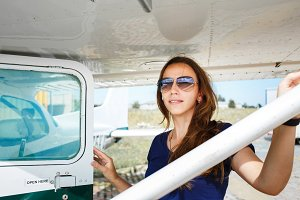 Young smiling woman standing near private plane