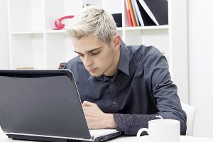 young man with computer laptop at the office or apartment