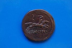 vintage Roman coin over blue