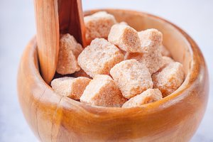 Brown cane sugar cubes in a wooden bowl