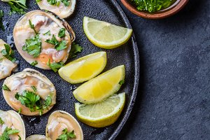 Raw clams with lemon, herbs and white wine, slate background