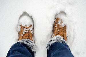 Man standing in yellow boots in snow, low section
