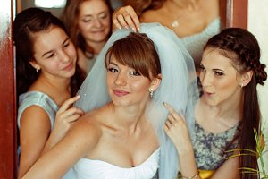 Bridesmaids play with bride's veil
