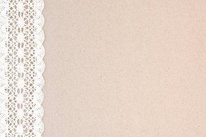 Vintage lace on cardboard texture.