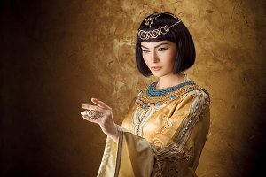 Beautiful Egyptian woman like Cleopatra pointing finger away on golden background