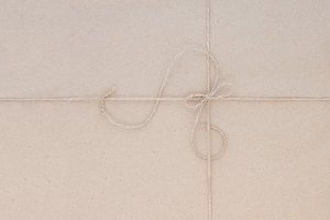 Cardboard packing with jute thread.