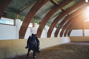 Female�riding�horse in indoor�riding hall