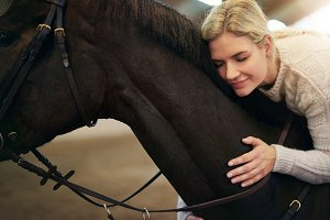 Female�with eyes closed�hugging dark�horse