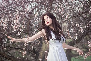 Beautiful girl standing at blossoming tree in the garden