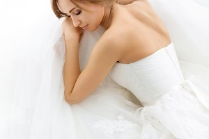Brides beauty. Young woman in wedding dress indoors