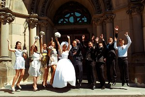 Bride, groom and friends jump