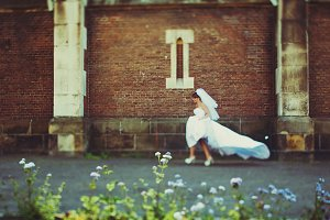 Bride runs along the brick wall