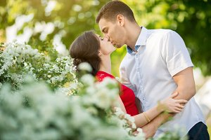Happy young couple kissing in park