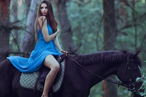 Beautiful woman riding horse in forest