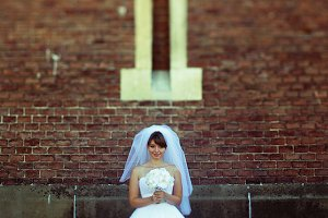 Bride standing under a small window