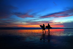 Surfers walking in the sunset