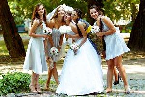 Bridesmaids lean to the bride