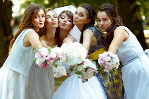 Pretty bridesmaids surround a bride