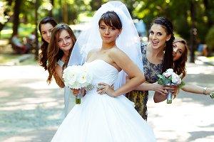 Bridesmaids hide behind a bride