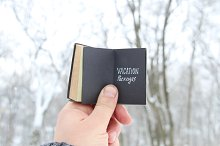 Vacation Packages. Vintage book with inscription on the background of winter forest