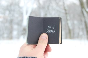 Let it snow lettering and Falling snow. Retro book with inscription.