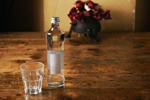 Bottle of water and glass in rustic kitchen