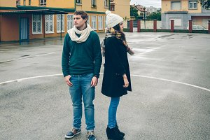 Serious young couple wearing winter clothes standing outdoors