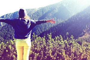 Girl feel freedom in mountains.
