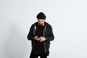 Young man in black looking on his smartphone