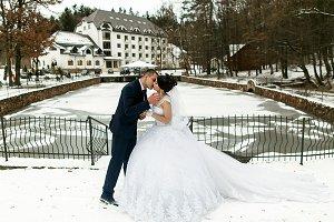 The brides kissing near frozen lake
