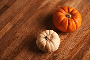 Two decorative pumpkins on wooden table